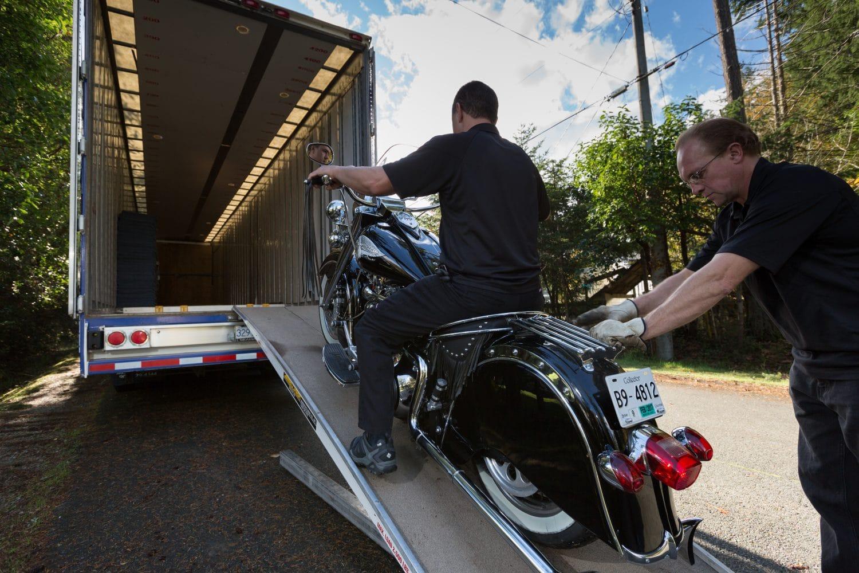 A. Breton carefully moving truck onto transport trailer